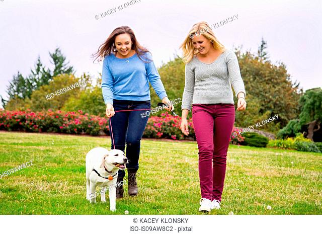 Two young women walking dog in park