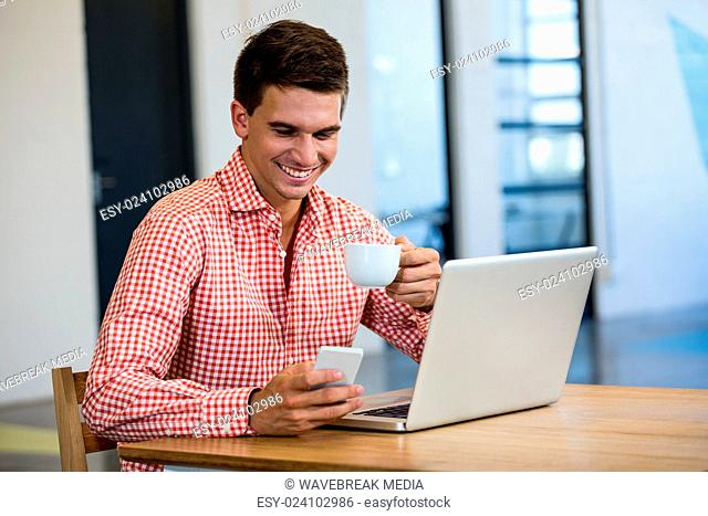 Man text messaging on mobile while having cup of coffee