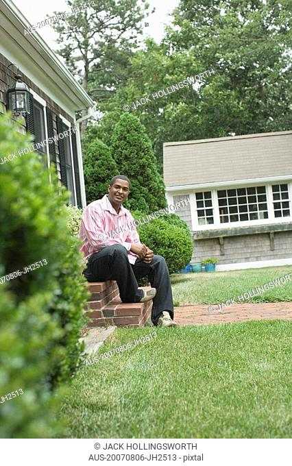 Mature man sitting on steps of a house