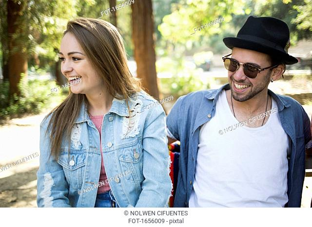 Happy couple sitting on bench in park
