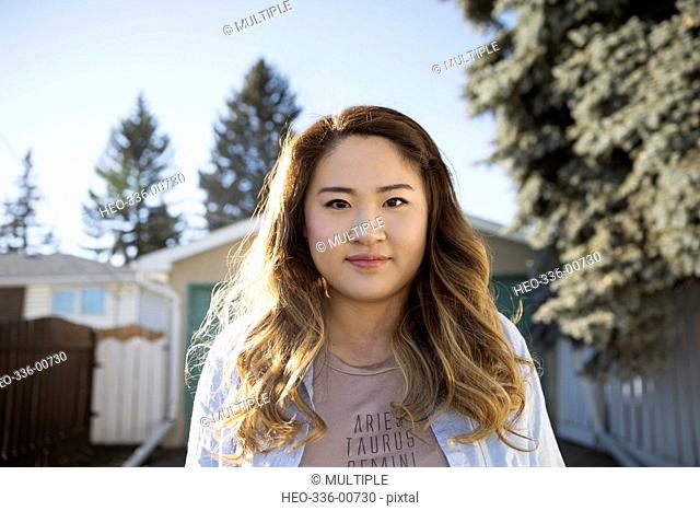 Portrait confident young Chinese woman in sunny driveway