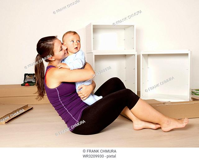 Young Mother with a Baby Moving to New Flat