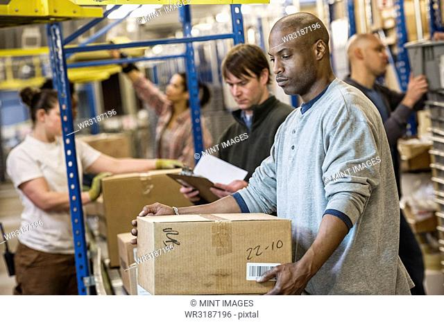 African American warehouse worker and a team of multi-ethnic workers working next to a motorized conveyor of cardboard boxes holding products in a large...
