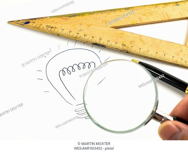 Drawn lightbulb, set square, ballpen and man's fingers holding magnifier