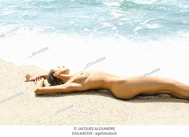 Naked young woman lying on sand at beach