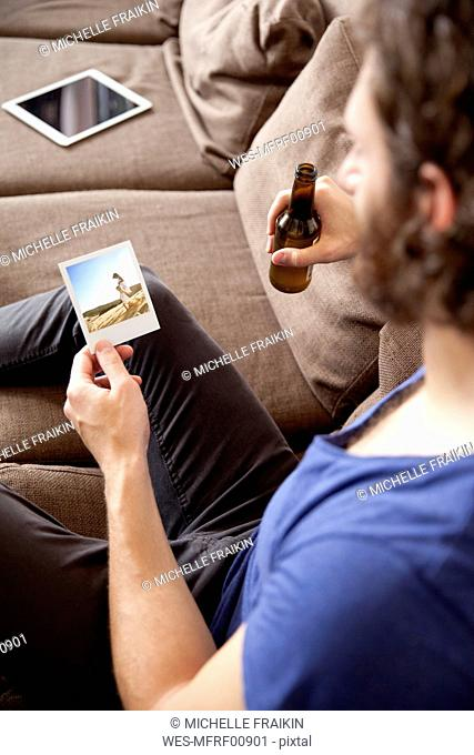 Man sitting on couch with beer bottle looking at instant photo