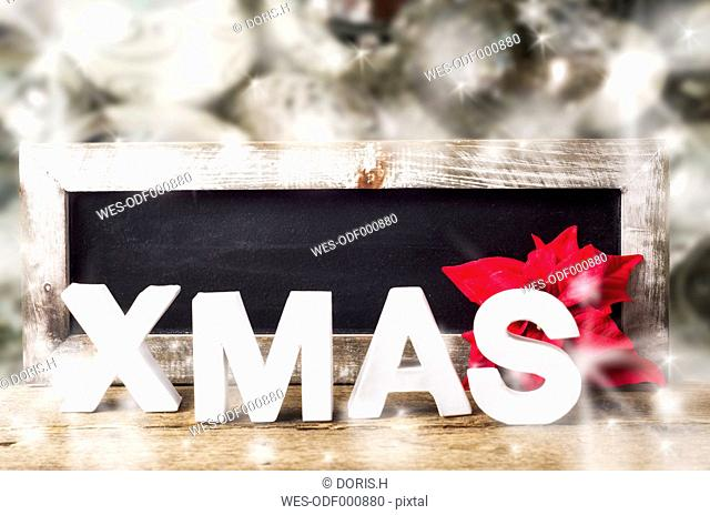 Blank blackboard with wooden frame, poinsettia and white letters building the word XMAS