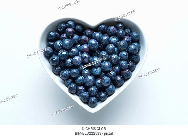 Blueberries in heart-shape bowl on white background