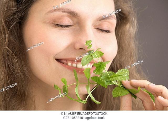 portrait of a young woman holding and smelling a sprig of mint