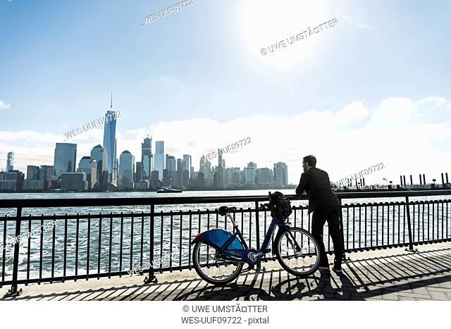 USA, man with bicycle at New Jersey waterfront with view to Manhattan