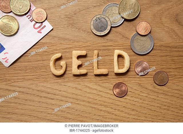 Geld, German for money, word written with biscuits, beside coins and a banknote