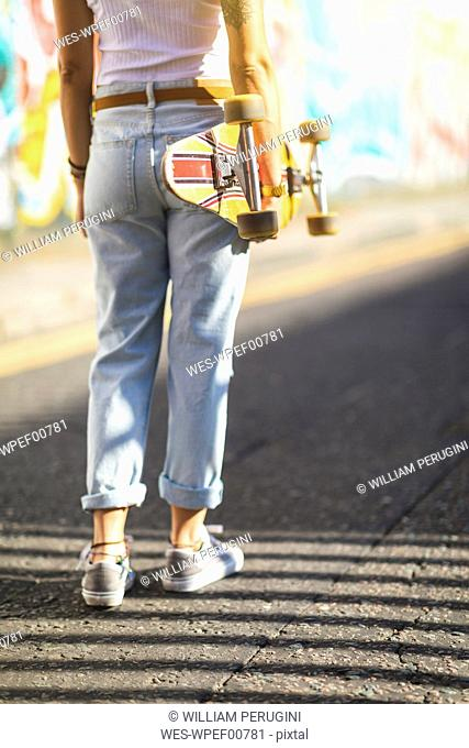 Rear view of young woman carrying skateboard in the city