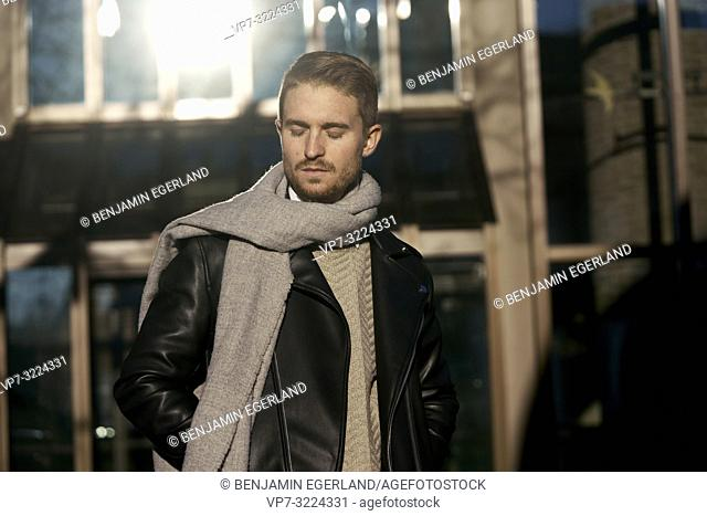 young fashionable man with closed eyed, sensitive emotion, wearing scarf outdoors in city, in Munich, Germany