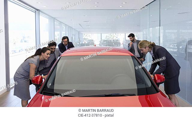 Customers looking at new car in car dealership showroom