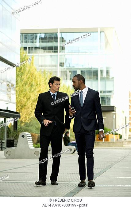 Businessmen having conversation while walking on sidewalk