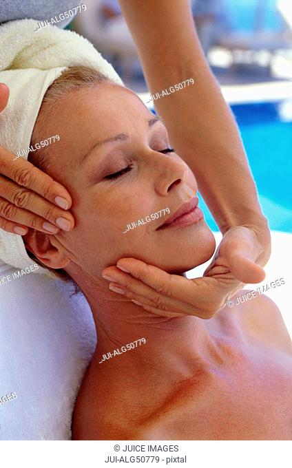 Woman receiving facial massage at spa