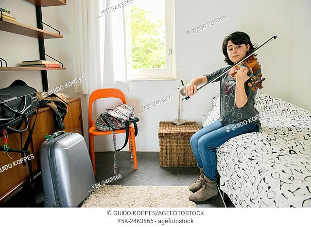 Tilburg, Netherlands. Female Italian violinist sitting on the bed of her Airbnb guest room, while practising with her violin