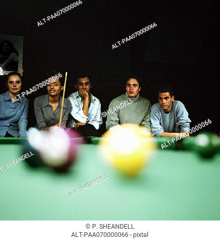 Group of young people watching a pool game, pool table blurred in foreground