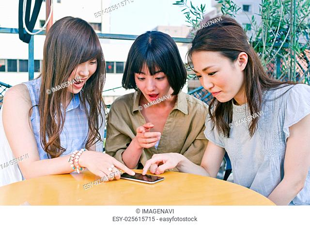 Women being surprised to see a smart phone