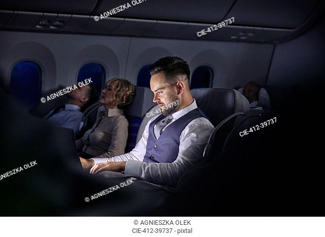 Businessman working on laptop on night airplane