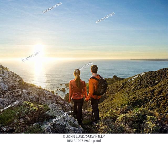 Hispanic couple watching sunset over water