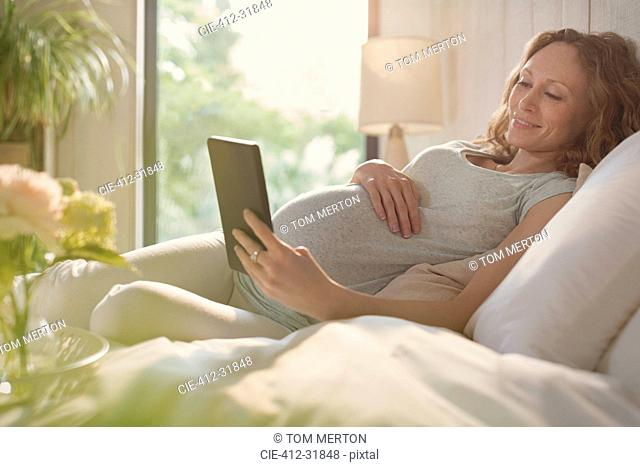Pregnant woman relaxing using digital tablet in sunny bedroom
