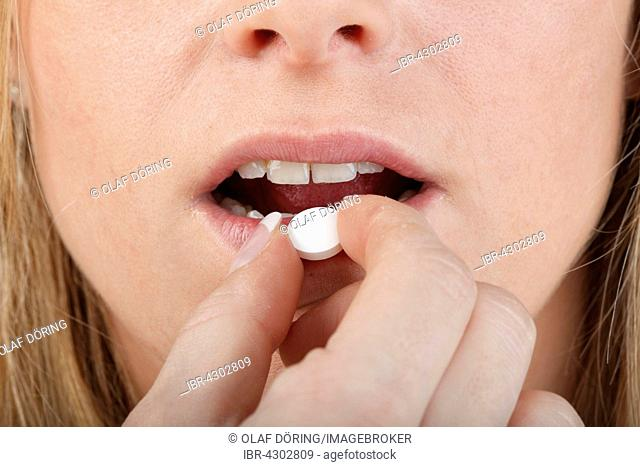 Close-up of young woman taking a pill