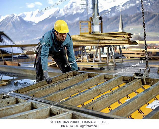 Construction worker lifting shuttering wall with crane, preparing framed formwork, Innsbruck Land, Tyrol, Austria