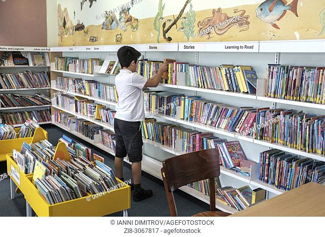 10 years schoolboy choosing books in public library. Surrey, England