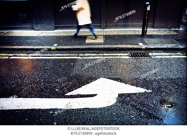 Unrecognizable person walking down the street with an arrow painted on the asphalt. London, England