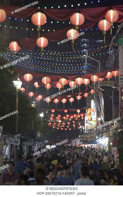 Crowd walking on the street decorated with Chinese lanterns at night, Chinatown, Singapore