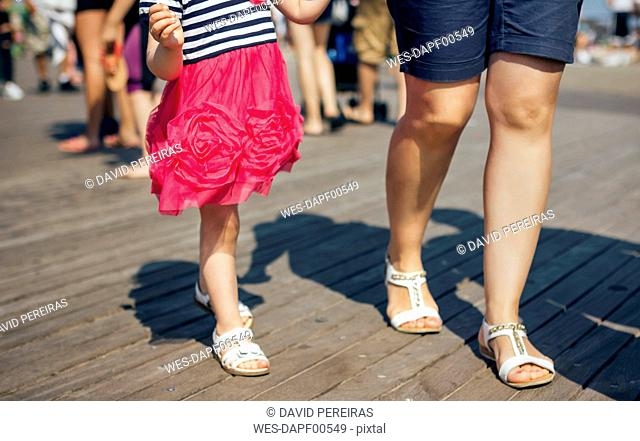 USA, New York, Coney Island, mother and little daughter walking on wooden walkway, partial view