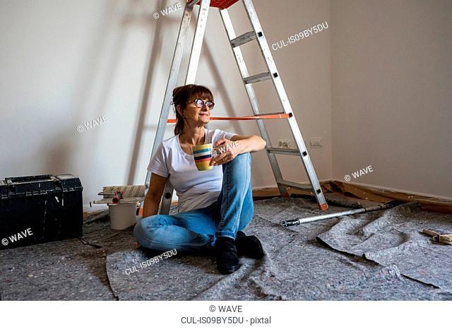 Senior woman sitting on floor taking coffee break from decorating house interior