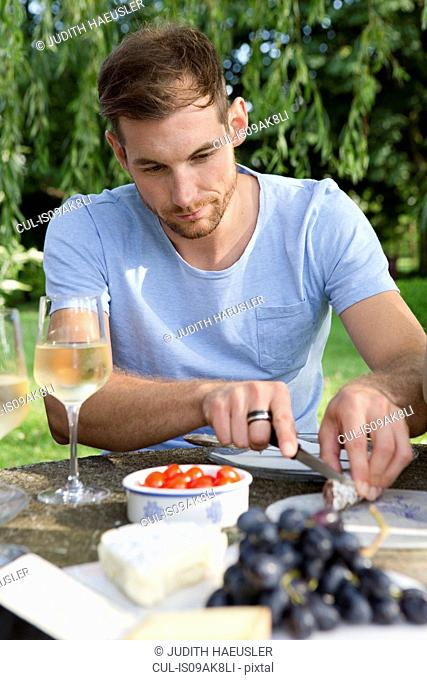 Mid adult man sitting at picnic table in garden