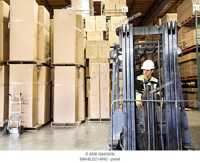 Caucasian worker driving forklift in warehouse