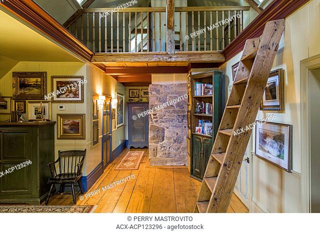 View of hallway with wide pinewood floorboards, Miller's stairs, bookcase and mezzanine on the upstairs floor inside an old circa 1805 Canadiana cottage style...