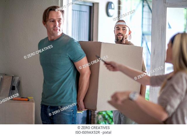 Moving house: two men carrying cardboard box