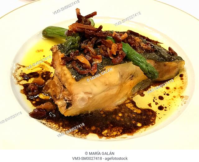 Turbot loin with Iberian ham and green asparagus. Spain