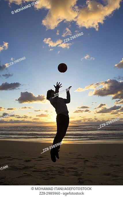Full length, silhouette of a little boy playing with the ball on the beach at sunset