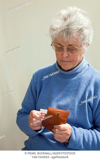 Europe  Senior woman pulling ten Euro note from a purse looking worried MR 09/05