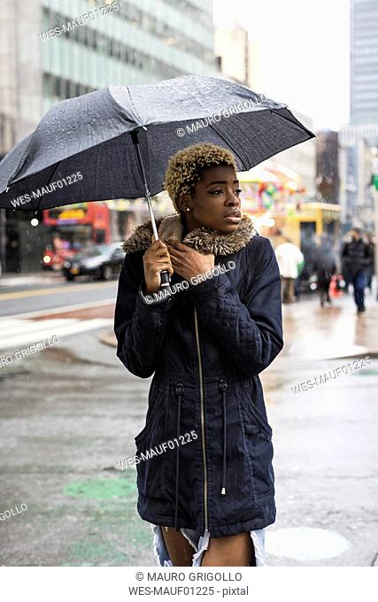 USA, New York City, portrait of young woman with umbrella on rainy day