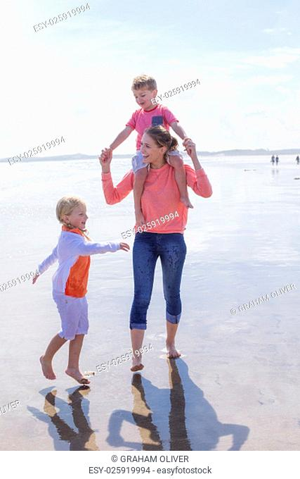 Happy single parent family walking along the beach. They are all laughing and smiling and walking across the waters edge