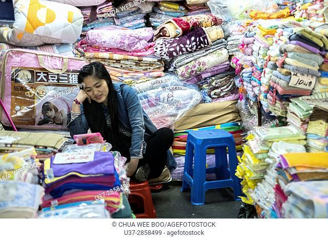 Female vendor selling blankets, Guangzhou, China