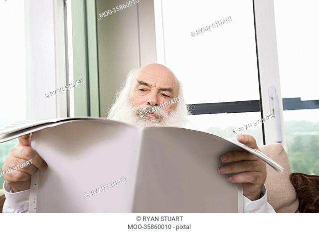 Senior man reading newspaper in house