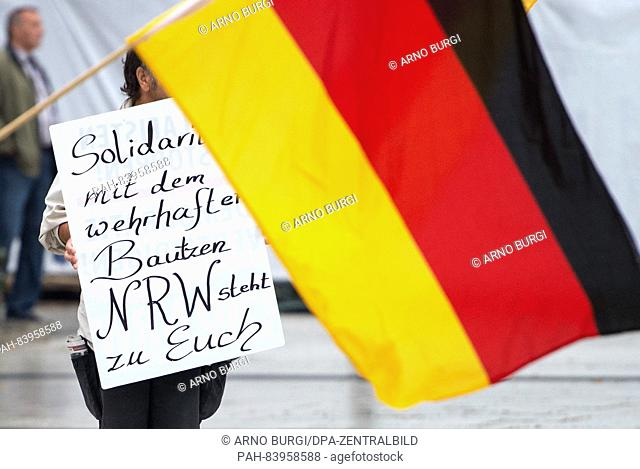 A man holding a placard expressing solidarity with a right-wing anti-immigration movement from German state North Rhine Westphalia and a German flag at a rally...