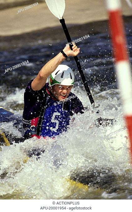 Competitor paddling through a kayak course