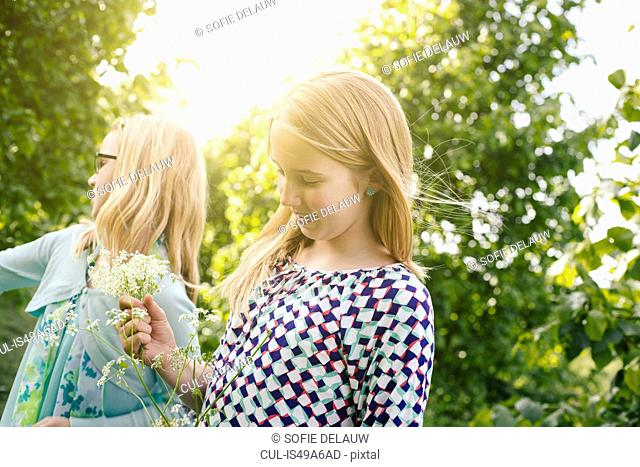 Two sisters strolling with bunches of wildflowers