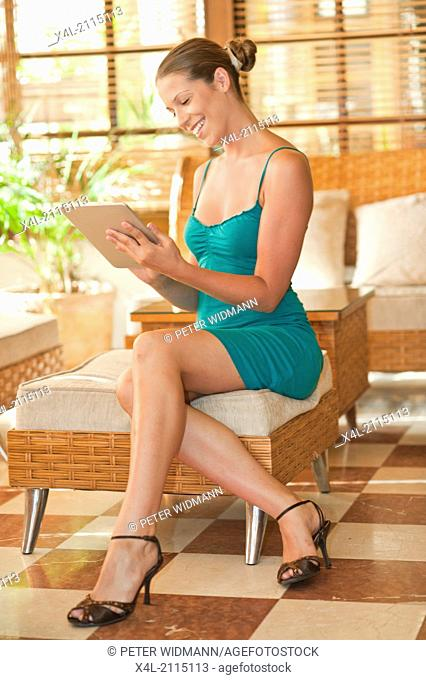 young, pretty woman on summer holiday, in lobby, with digital tablet, surfing the net (model-released)