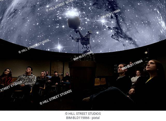 Students watching stars in planetarium