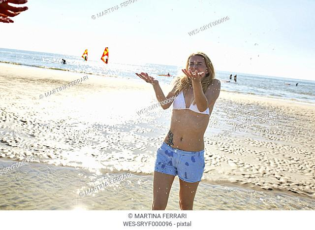 Happy young woman being splashed with water on the beach
